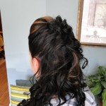 back view of girls long dark curled hair half pinned back
