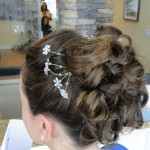 back view of updo hairstyle with curls and flower pins