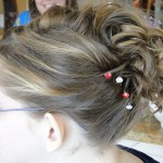 close up of updo hairstyle with curls and rhinestone bobbypins