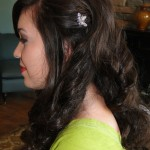side profile of brunette with curly hair and clipped back on side