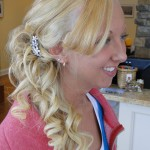 side profile of blonde curly hairstyle with part of it pinned back