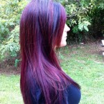 side profile of girl in black shirt with long dark hair with purple highlights